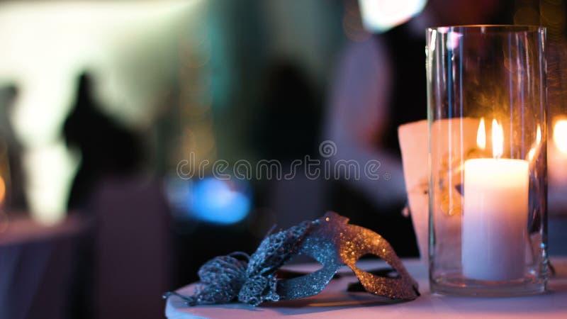 A máscara venetian do ouro do disfarce encontra-se em uma tabela em um clube noturno durante um partido do traje, vela branca que filme