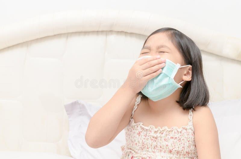 Máscara y estornudo de la protección del desgaste de la muchacha foto de archivo