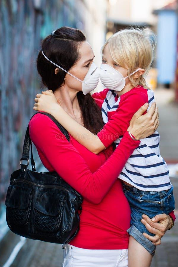 Máscaraes protetoras vestindo da mulher e do filho foto de stock