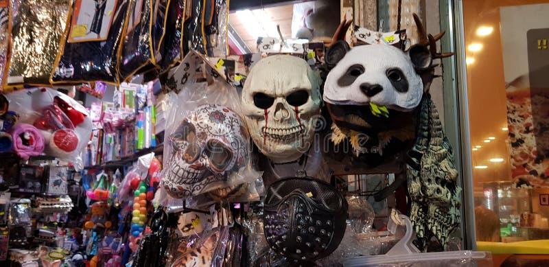 Máscaras assustadores e o outro material colorido plástico para as crianças expostas para a venda em uma loja antes do disfarce j fotos de stock