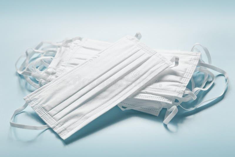 Máscaras brancas de segurança empilhadas sobre fundo azul Coronavírus, gripe, filtro de poluição do ar Equipamento de proteção in fotografia de stock