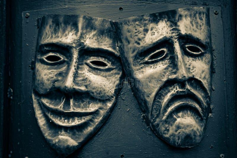 Máscaras de acero de la comedia y de la tragedia pintadas en colores de oro y azul marino fotografía de archivo