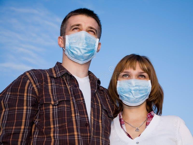 Máscaras de la gripe de los pares que desgastan imagenes de archivo