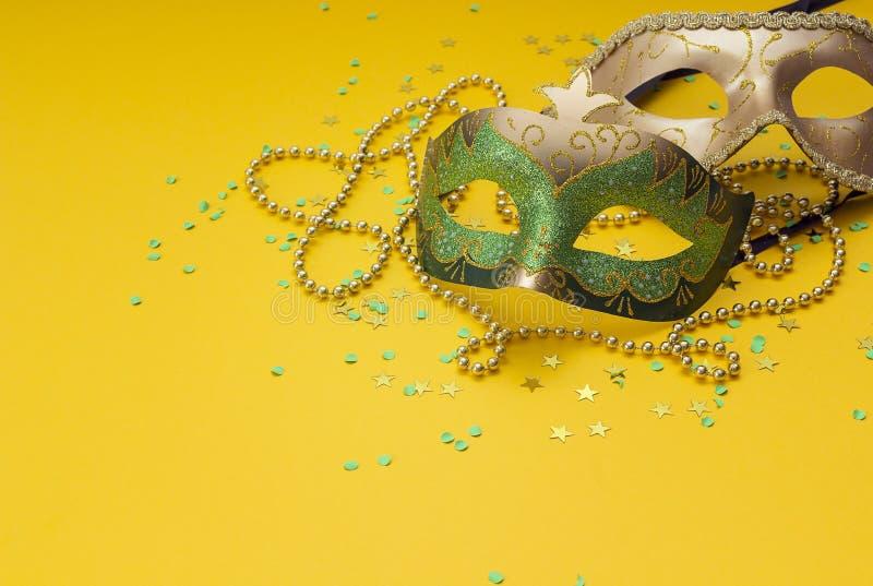 Máscaras e grânulos do carnaval em um fundo amarelo Espaço para o texto fotografia de stock royalty free