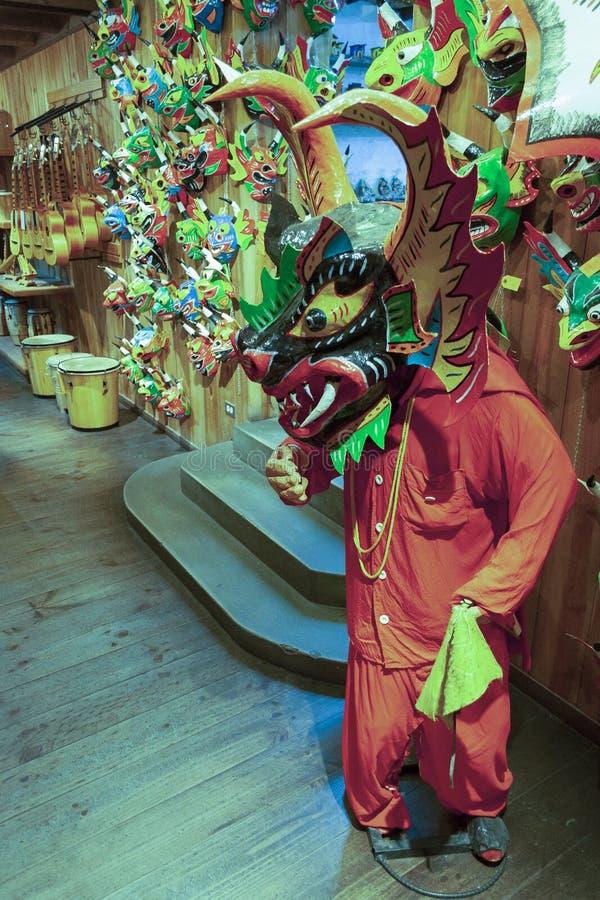 Máscaras icónicas y maniquíes que llevan los trajes de los diablos maniobrables que bailan Corpus Christi en una tienda de souven imagen de archivo