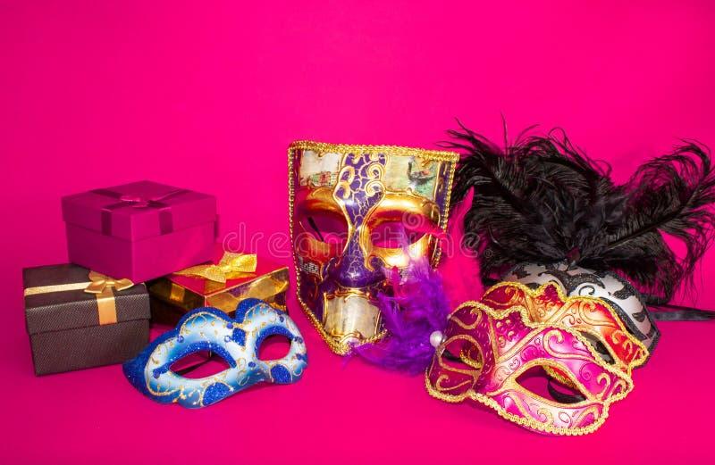 Máscaras y regalos del carnaval en un fondo rosado fotografía de archivo libre de regalías