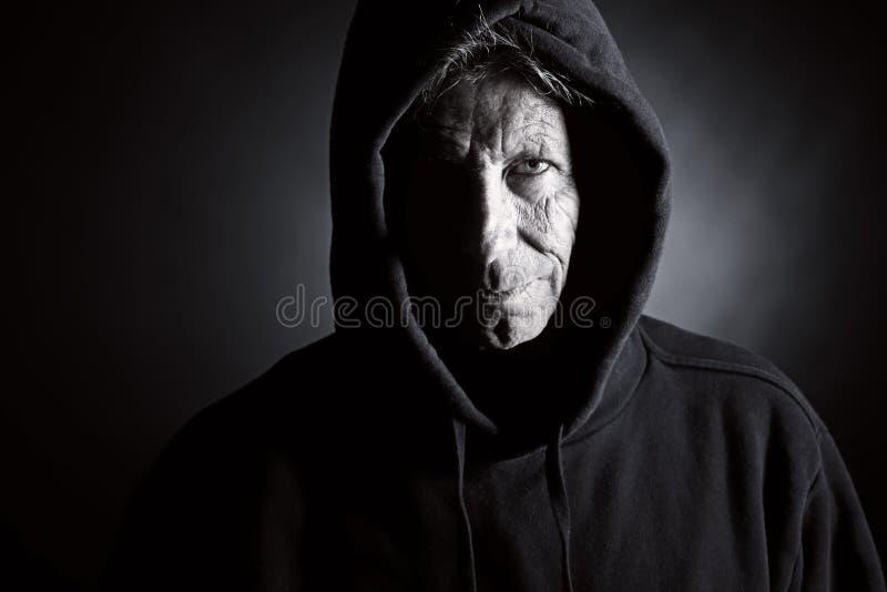 Mâle aîné de intimidation dans le dessus à capuchon photos libres de droits