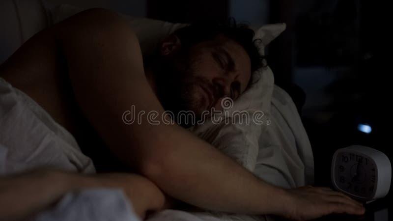 Mâle adulte somnolent essayant d'arrêter le réveil, manque de sommeil, effort images libres de droits