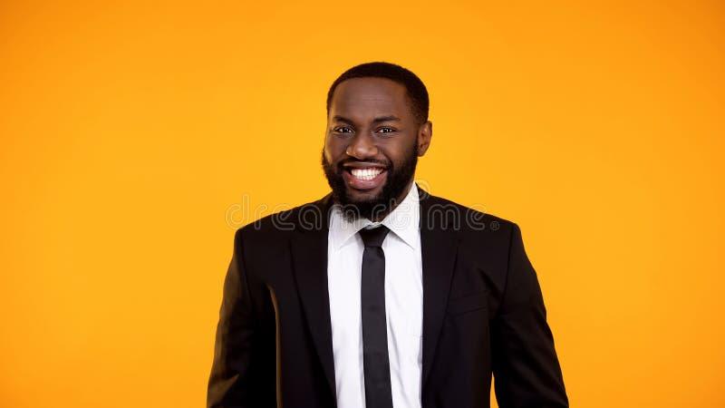 Mâle africain beau dans le formalwear souriant gaiement à la caméra, calibre d'annonce image stock