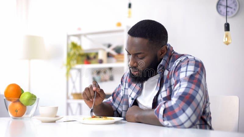 Mâle afro-américain bouleversé mangeant des spaghetti sur le déjeuner, crise de relations, problème photographie stock libre de droits