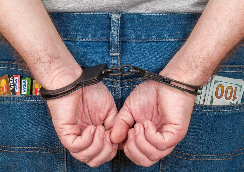 Mâle arrêté dans des menottes derrière elle de retour avec des cartes de crédit et photos libres de droits