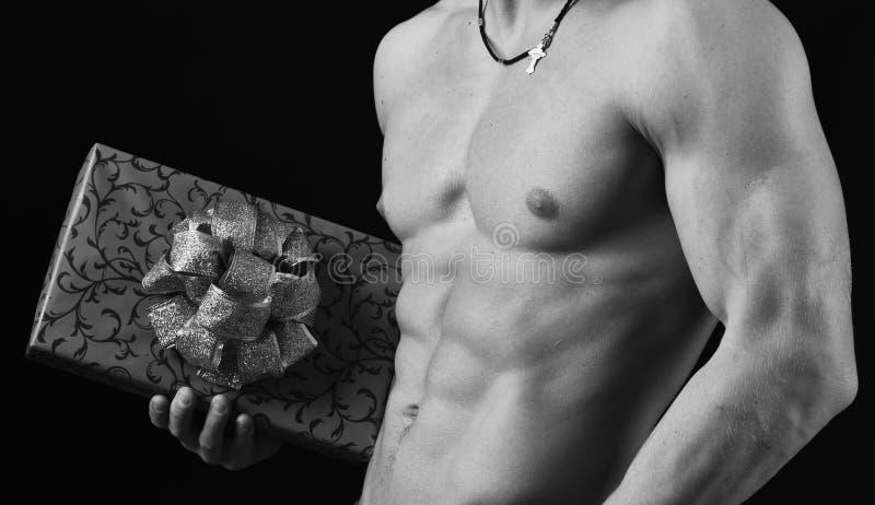 Mâle avec le torse nu d'isolement sur le fond noir Corps d'athlètes dans la fin, main tenant le boîte-cadeau rouge photographie stock libre de droits