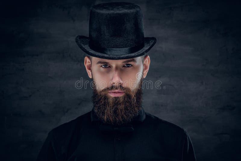 Mâle barbu avec le tatouage sur son cou et cylindre de chapeau supérieur sur le hea images libres de droits