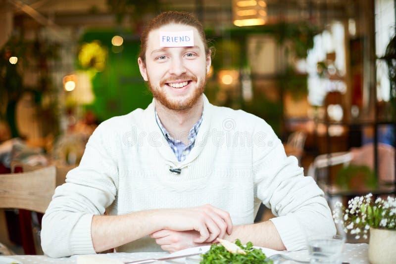 Mâle barbu dans le chandail jouant en café avec le papier de chutes sur des fronts photos stock