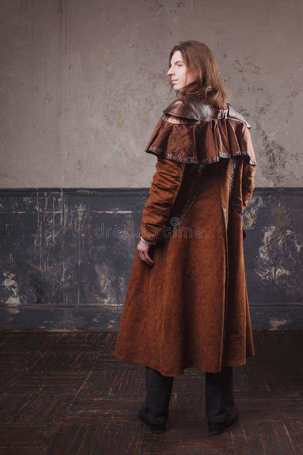 Mâle beau dans le manteau brun, style de punk de vapeur Rétro portrait d'homme au-dessus de fond grunge photos stock