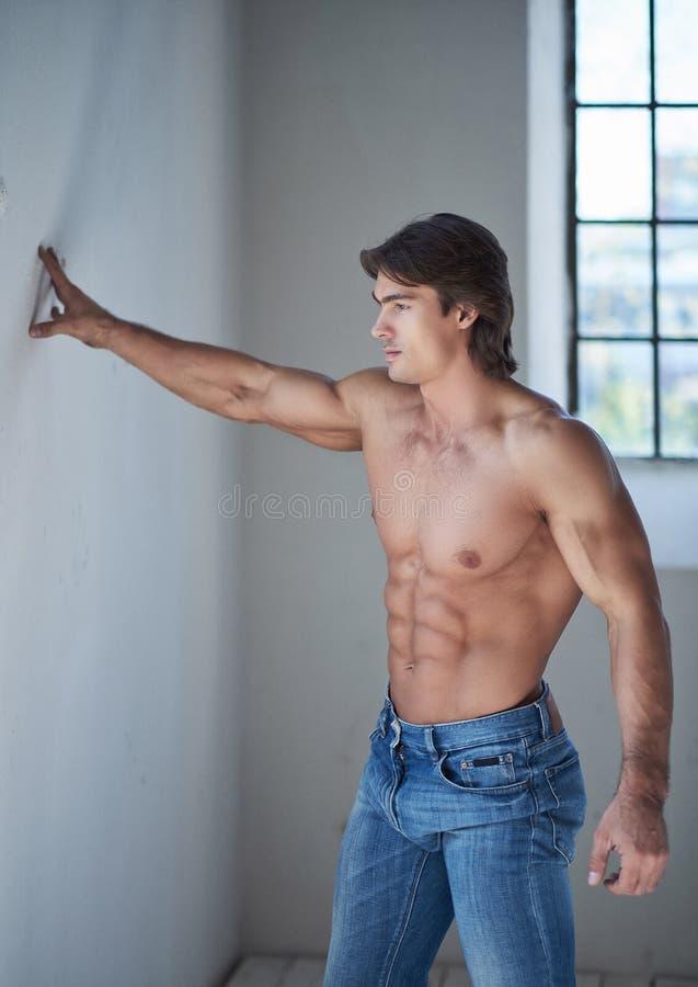 Mâle beau sans chemise avec un corps musculaire parfait se penchant sur un mur dans le studio, regardant une fenêtre images stock