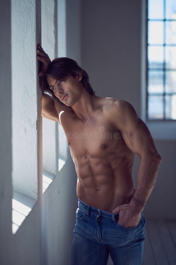 Mâle beau sans chemise avec un corps musculaire parfait se penchant sur un mur dans le studio, regardant une fenêtre image libre de droits