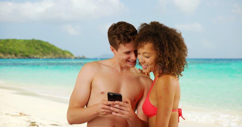 Mâle caucasien beau avec l'ami féminin à l'aide du smartphone sur la plage images stock