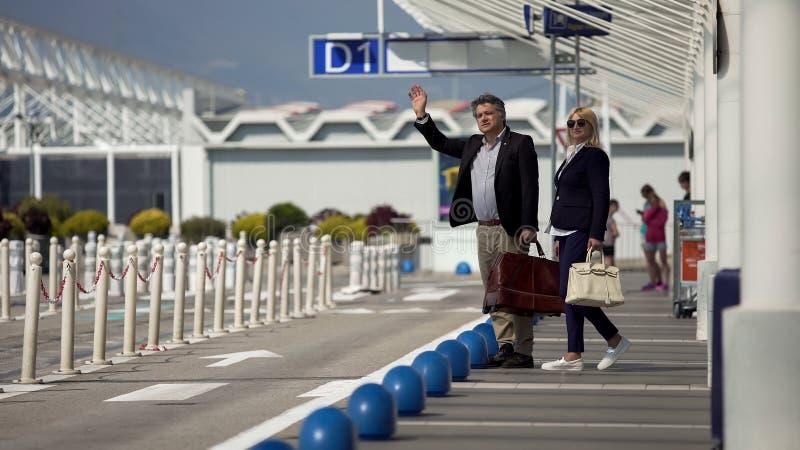 Mâle d'une cinquantaine d'années et taxi partant femelle d'aéroport et de salut, voyageant images libres de droits