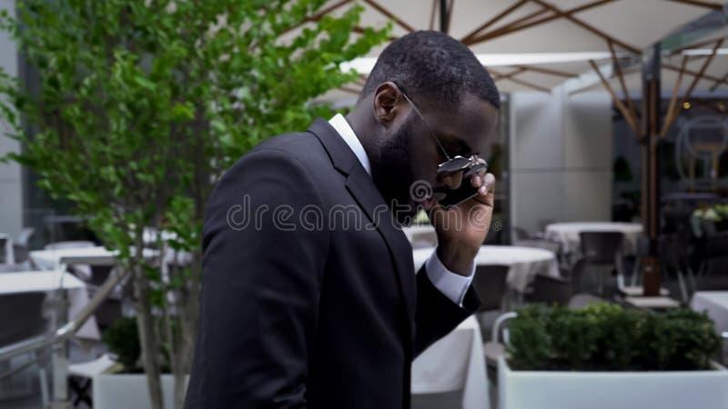 Mâle dans le costume passant par le café de luxe d'air ouvert parlant au-dessus du téléphone portable image stock