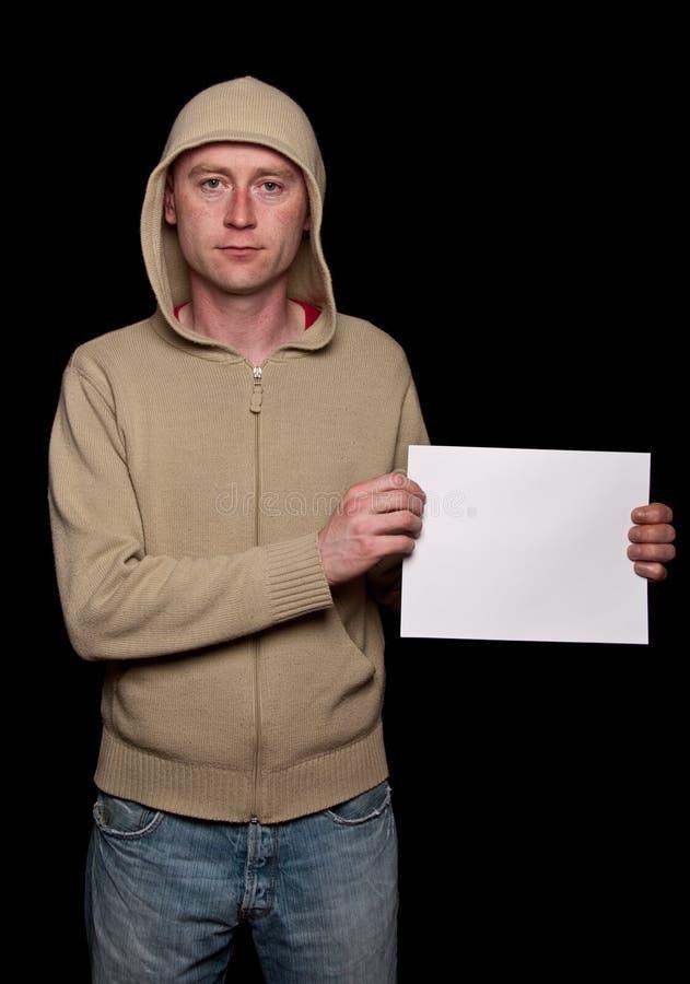 Mâle dans un hoodie retenant l'espace blanc d'annonce image libre de droits