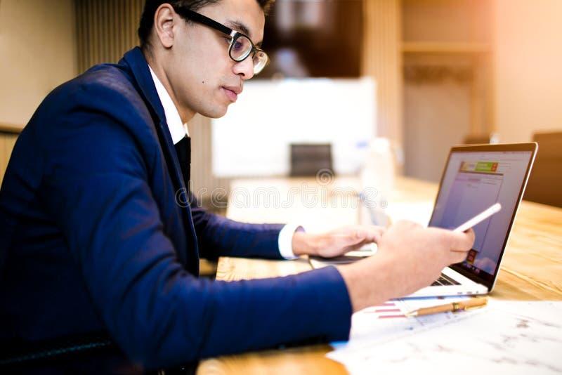 Mâle en texte de dactylographie d'employeur réussi de costume sur le téléphone portable pendant l'utilisation du carnet images libres de droits