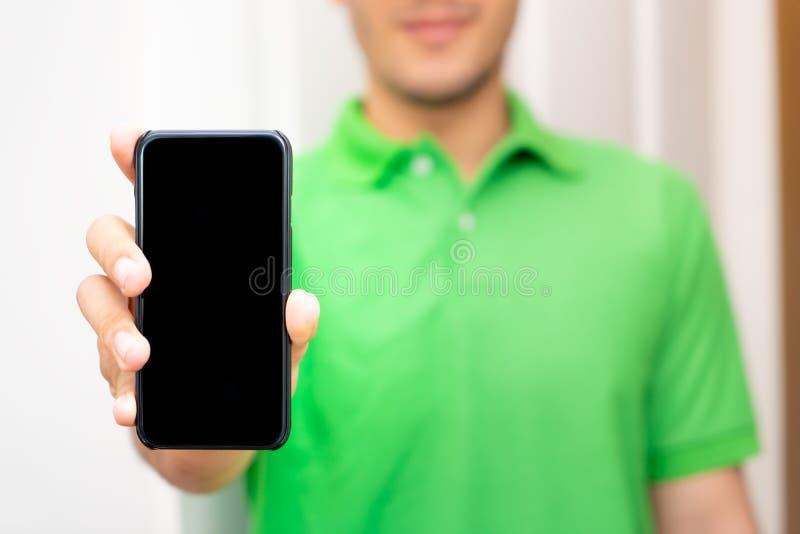 Mâle en vert tenant la moquerie mobile noire d'écran  image libre de droits