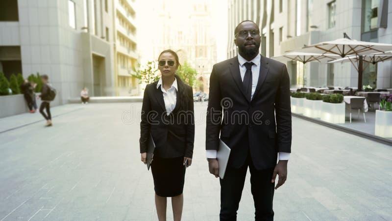 Mâle et agents fédéraux féminins marchant avec la garantie pour arrêter le suspect, sécurité photographie stock