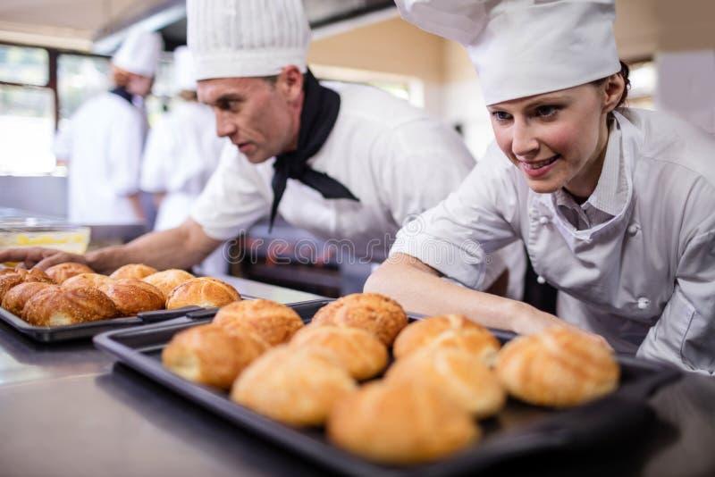 Mâle et chefs féminins préparant des petits pains de kaiser dans la cuisine photographie stock libre de droits