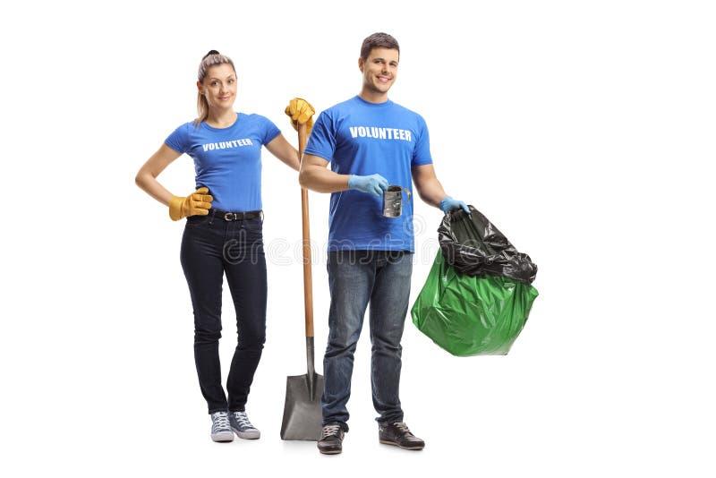 M?le et volontaires f?minins avec un sac de pelle et de d?chets photos libres de droits