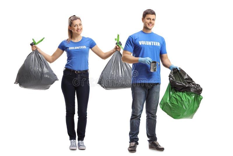 M?le et volontaires f?minins nettoyant et tenant des sacs de d?chets images stock
