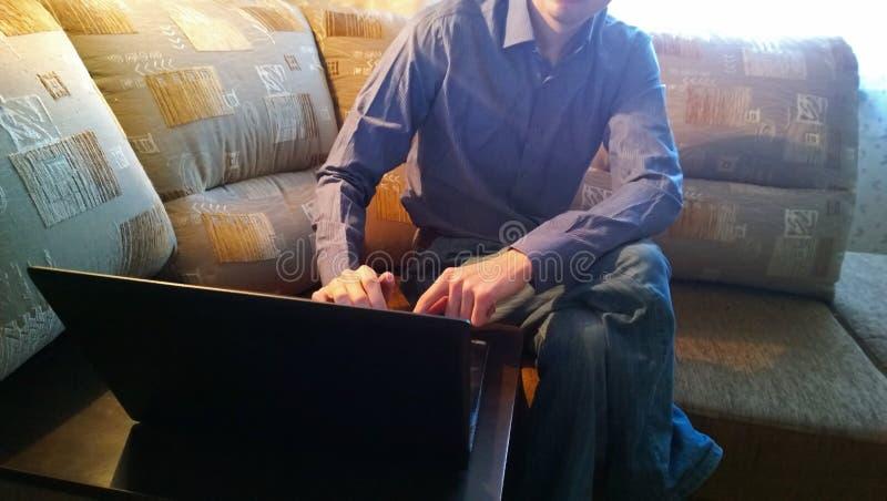 Mâle-indépendant s'asseyant sur le sofa et le travail image stock
