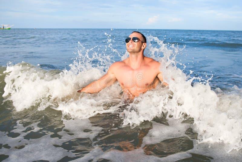 Mâle musculaire heureux appréciant la mer images stock