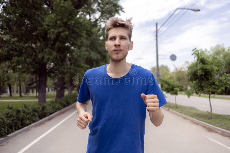 Mâle occasionnel masculin faisant le fonctionnement de matin dans les allées de rue de ville photo libre de droits