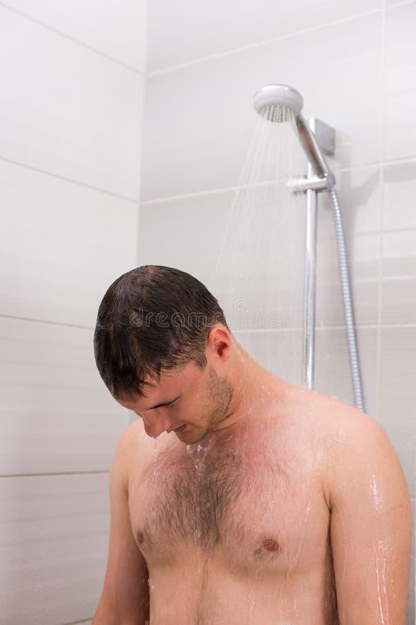 Mâle prenant une douche dans la salle de bains photographie stock libre de droits