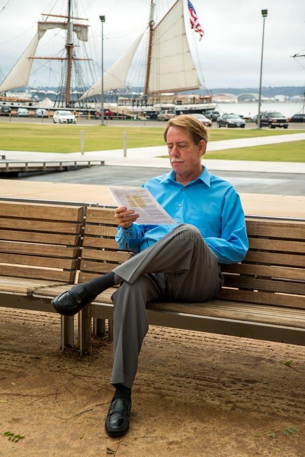 Mâle s'asseyant sur un banc lisant un document images libres de droits