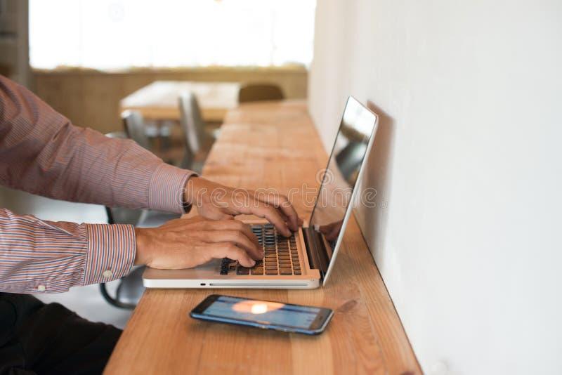 Mâle supérieur asiatique utilisant l'ordinateur portable en café photo stock