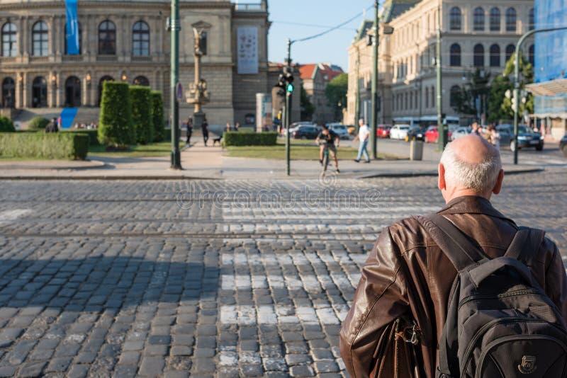 Mâle supérieur avec le sac à dos marchant les rues de la ville de Prague Voyage de retraite photographie stock libre de droits