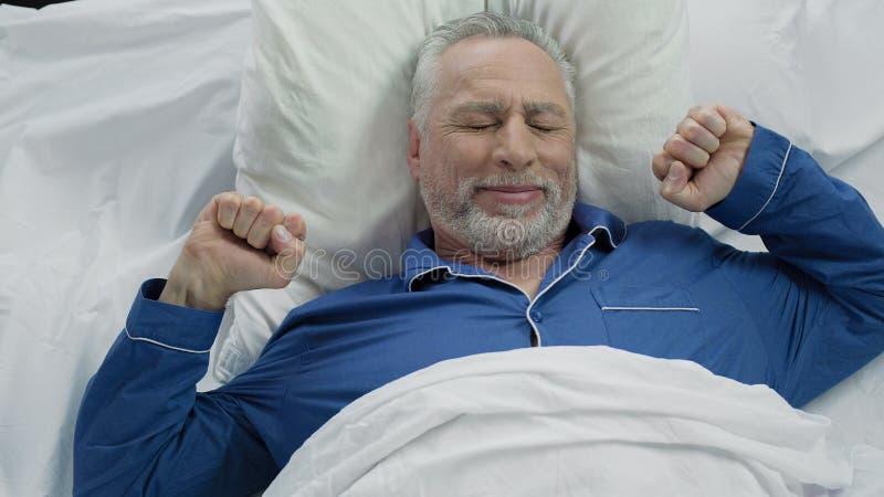 Mâle supérieur heureux se réveillant dans la bonne humeur à la maison après nuit calme agréable photo stock