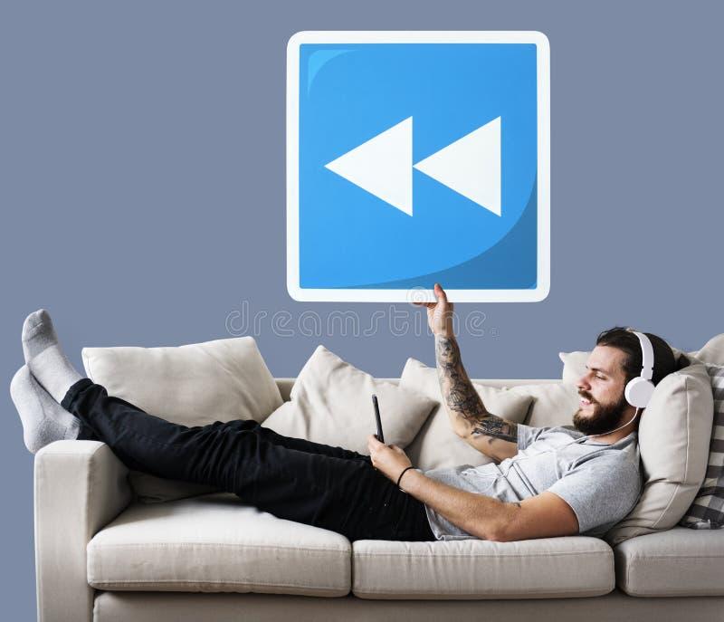 Mâle sur un divan tenant une icône de bouton de rebobinage photographie stock