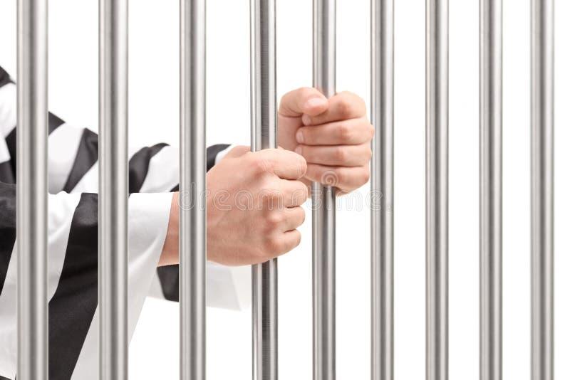 Mâle tenant des barres de prison photos stock