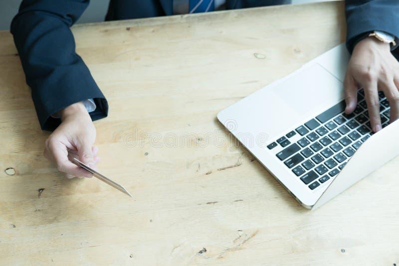 Mâle tenant une carte de crédit et à l'aide de l'ordinateur portable pour en ligne photographie stock