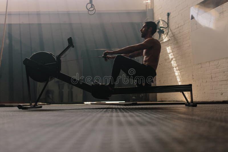 Mâle utilisant la machine à ramer au centre de fitness image stock