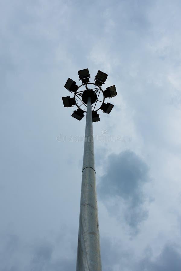 Mât avec des projecteurs sur le stade et le fond foncé de ciel photos libres de droits