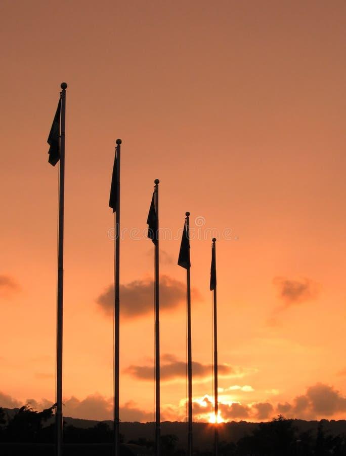 Mâts de drapeau et coucher du soleil photos stock