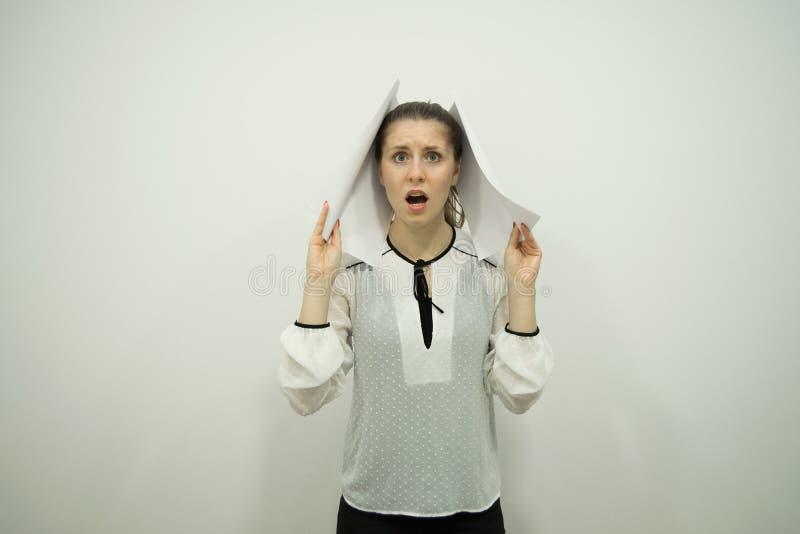 Mädchen steht mit ihrem Mund, der in der Überraschung offen ist, die in beiden Handblättern des Weißbuches in einem weißen Büro h lizenzfreies stockbild