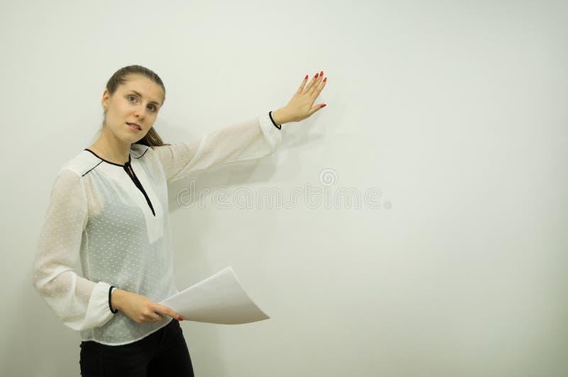 Mädchen stellt etwas bei der Stellung auf dem links gegen eine weiße Wand dar, die Blätter in einer Hand hält stockbilder