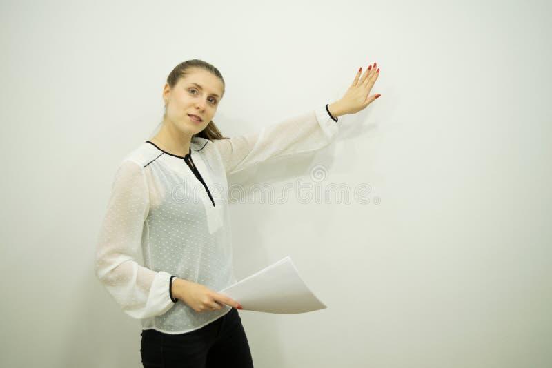 Mädchen stellt etwas beim Bereitstehen einer weißen Wand dar, die Blätter in einer Hand hält und mit der anderen Hand darstellt stockbild