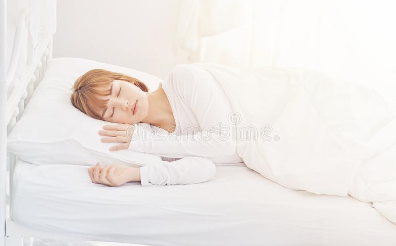 Mädchen tragen weiße Pyjamas Schlafen auf dem Bett lizenzfreie stockfotografie