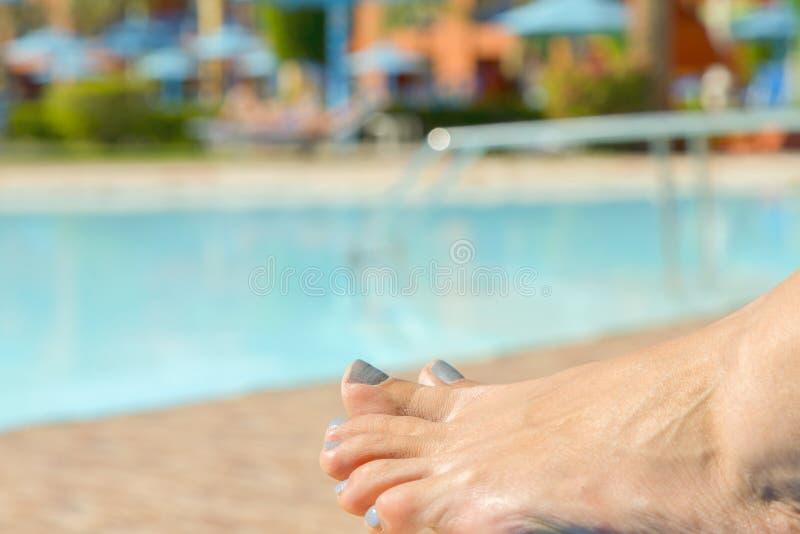 Mädchenbeine durch Pool Entspannung am Pool Die Füße der Frau gegen Swimmingpool auf dem Stillstehen lizenzfreie stockbilder